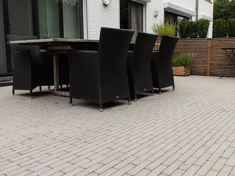 terras met klinkers, tafel en riete stoelen