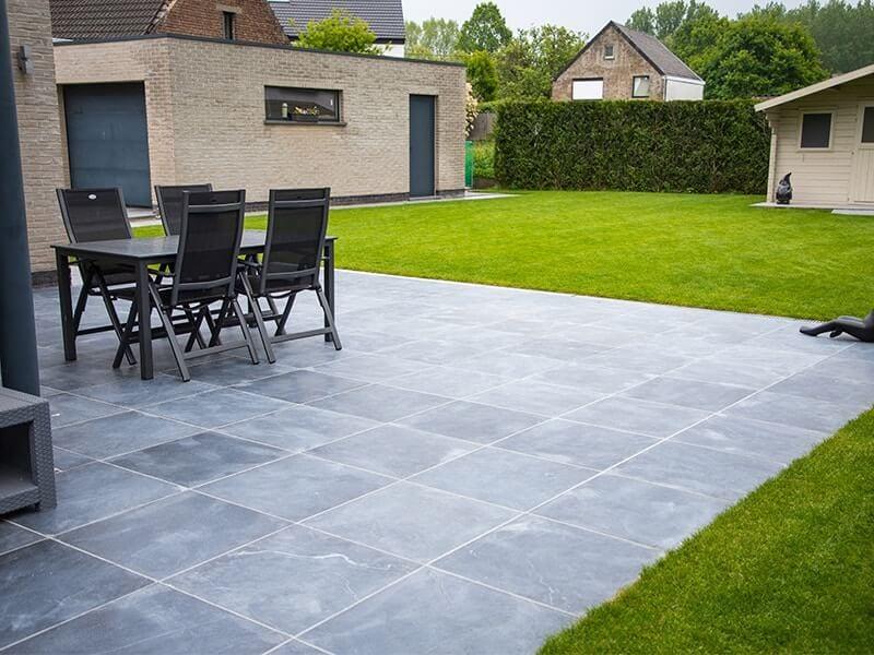 terras natuursteen met gazon, tuinstafel, tuinhuis en garage
